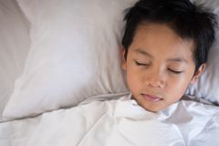 Boy sleeping on bed with white sheet and pillow. Asian kid fall asleep daydreaming.sleep concept Stock Images