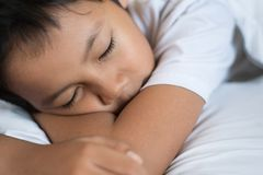 Boy sleeping on bed with white sheet and pillow. Asian kid fall asleep daydreaming. Sleep concept Royalty Free Stock Photos