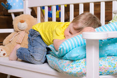 Boy sleeping on bench indoors Royalty Free Stock Photography