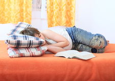 Boy sleeping with a book. Sleeping kid - tired boy lying with a book on bed Royalty Free Stock Image
