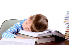 Boy sleeping on a books. Little boy fell asleep on a large open book. boy 5 years. on the desk a lot of books. photo taken on a light background close-up Stock Photos