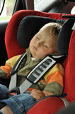 Boy sleeping in child car seat Stock Photos