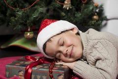 Boy sleeping  at the Christmas gift Stock Image