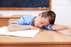 Boy sleeping in classroom Stock Photo