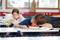 Boy Sleeping On Desk In Classroom Stock Photos