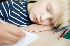 Boy sleeping while doing his homework in notebook. Boy sleeping on the desk while doing his homework in notebook. Close up Stock Photography