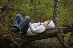 Boy sleeping in forest. Teenage boy sleeping on fallen tree trunk in forest Royalty Free Stock Images