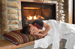 Boy sleeping in front of fireplace Royalty Free Stock Images