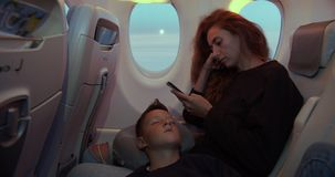 Boy sleeping on hands of mother while having flight in airplane.