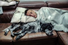A boy sleeping with his dog stock photo