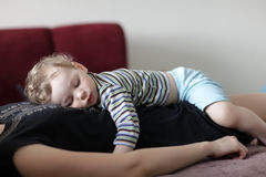 Boy sleeping on his mother Royalty Free Stock Images