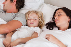 Boy sleeping between his parents Royalty Free Stock Image
