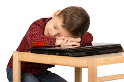 Boy sleeping on the laptop. Tired little boy sleeping on the laptop computer isolated on white background Stock Photos