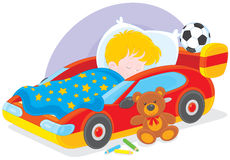 Boy sleeping. Little boy sleeps in his bed made as a sport car Royalty Free Stock Image