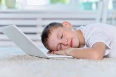 boy sleeping near and  laptop Stock Photography