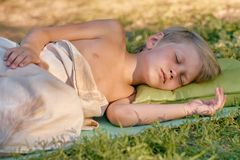 Boy sleeping outdoor on tourist pillow. Tired little boy sleeping after playing outdooron tourist pillow Royalty Free Stock Photography
