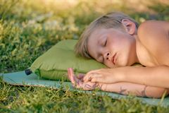 Boy sleeping outdoor on tourist pillow. Tired little boy sleeping after playing outdooron tourist pillow Royalty Free Stock Images