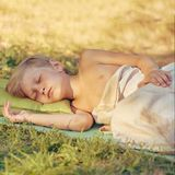 Boy sleeping outdoor on tourist pillow. Tired little boy sleeping after playing outdooron tourist pillow, image with toning and square aspect ratio Stock Photo