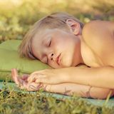 Boy sleeping outdoor on tourist pillow. Tired little boy sleeping after playing outdooron tourist pillow, image with toning and square aspect ratio Stock Images