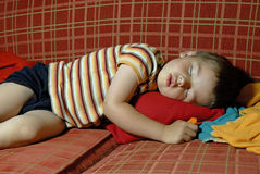 Boy sleeping on a red sofa. Young Boy sleeping on a red sofa Royalty Free Stock Photos
