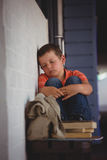 Boy sleeping while sitting on bench by wall Royalty Free Stock Photo