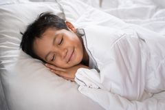 Boy sleeping with smile face on white bed sheet and pillow. Boy fall asleep with smiling face having sweet dream.sleep concept Royalty Free Stock Photography