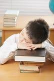 Boy sleeping on stack of books Royalty Free Stock Photo