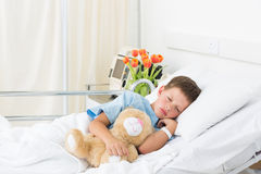 Boy sleeping with teddy bear in hospital Royalty Free Stock Image