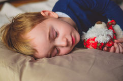 Boy  sleeping  with toy Stock Photos