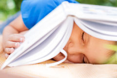 Boy sleeping under opened book Royalty Free Stock Photo