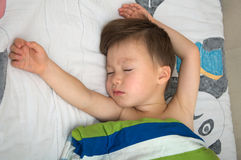 Boy sleeping  with widespread hands Royalty Free Stock Images