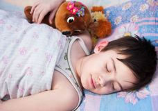 The boy sleeps in a bed. With a toy bear Royalty Free Stock Images