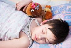 The boy sleeps in a bed. With a toy bear Stock Image
