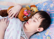 The boy sleeps in a bed. With a toy bear Royalty Free Stock Photography