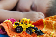 Boy sleeps with bulldozer toy. Little bulldozer toy and boy sleeps in background Royalty Free Stock Photos