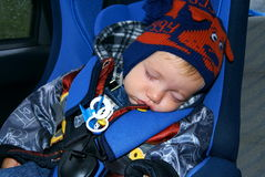 The boy sleeps in the car. The baby in autumn clothes sits in a children's autoarmchair and sleeps Royalty Free Stock Photography