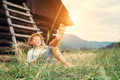 Boy sleeps in grass under hayloft in summer afternoon Royalty Free Stock Image