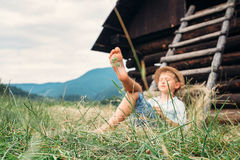 Boy sleeps in grass under hayloft in summer afternoon Royalty Free Stock Images