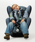 Boy sleeps in safe auto chair. Isolated on grey background Stock Images