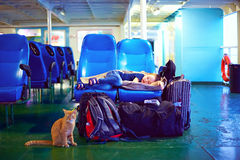 Boy sleeps on seats during exhausting journey on ferry boat Stock Images