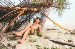 Boy sleeps in selfmade hut on tropical beach Stock Image