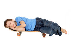 A boy sleeps on a skateboard Royalty Free Stock Image