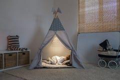 Boy sleeps in the teepee. The boy sleeps in the teepee playroom in the lamplight stock photos