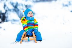 Boy on sleigh ride. Child sledding. Kid with sledge. Little boy enjoying a sleigh ride. Child sledding. Toddler kid riding a sledge. Children play outdoors in stock image