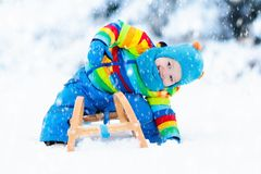 Boy on sleigh ride. Child sledding. Kid with sledge Stock Images