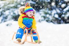 Boy on sleigh ride. Child sledding. Kid with sledge. Little boy enjoying a sleigh ride. Child sledding. Toddler kid riding a sledge. Children play outdoors in Royalty Free Stock Photography