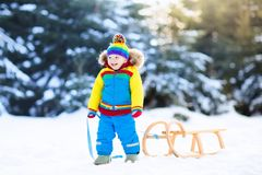 Boy on sleigh ride. Child sledding. Kid with sledge Stock Image