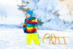 Boy on sleigh ride. Child sledding. Kid with sledge Royalty Free Stock Images