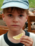 Boy and a slice of lemon. A young boy looks into the camera, wearing a cap and a small slice of lemon in his hand Stock Photo