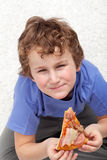 Boy with a slice of pizza Stock Image